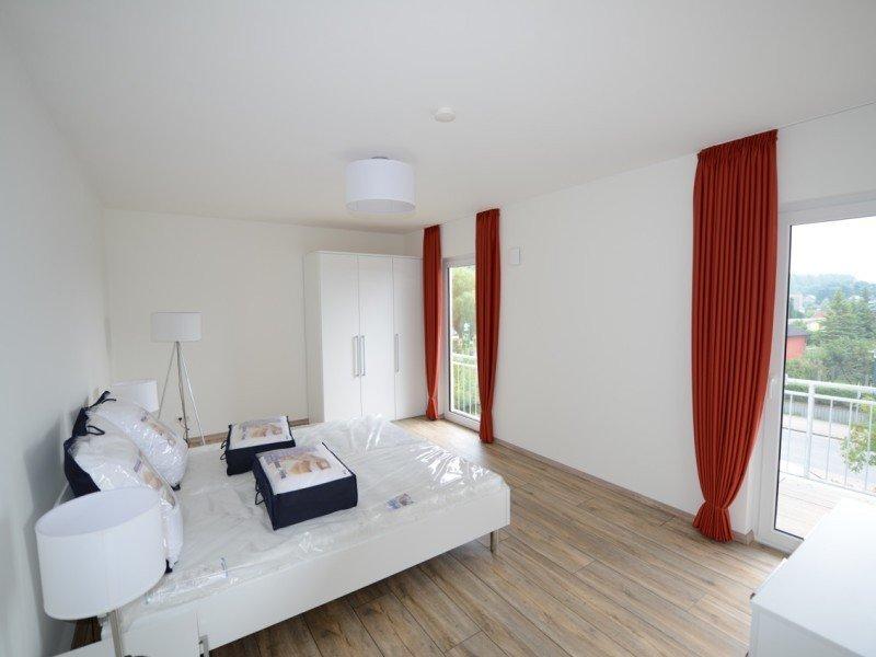 Schlafzimmer mit großem Doppelbett und bodentiefen Fenstern